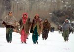 Some women can be seen carefully walking on the thick sheath of ice covering the Gojal Lake