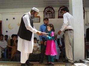Executive District Officer Primary and Secondary Education Haji Siraj Muhammad giving away certificates to a position holder