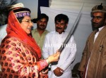 Federal Information Minister checks the sharpness of a sword at GB stall